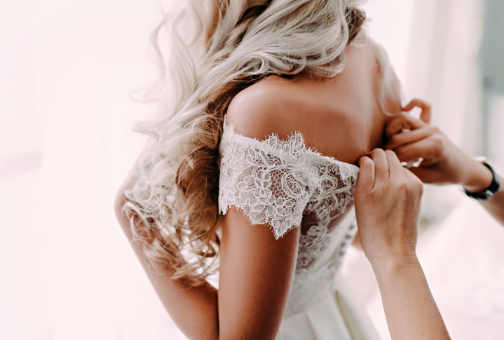 A wedding dress being done up
